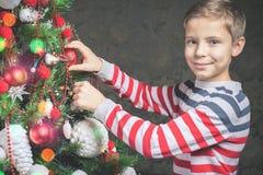 Stående av den lyckliga pojken som dekorerar julgranen, iklädd tröja Royaltyfria Bilder