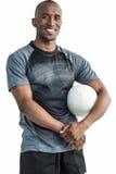 Stående av den lyckliga säkra idrottsmannen med rugbybollen Royaltyfri Bild