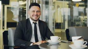 Stående av den lyckliga skäggiga Caucasian affärsmannen i formell kläder som sitter, dricker kaffe och ler i glas- kafé arkivfilmer