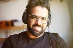 Stående av den lyckliga skäggiga mannen i hörlurar som hemma lyssnar till musik Koppla av och vilotidbegrepp _ Arkivbild
