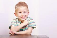 Stående av den lyckliga skratta blonda pojkebarnungen på tabellen Arkivbilder