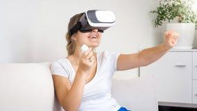 Stående av den lyckliga skratta unga kvinnan som kopplar av på soffan och den hållande ögonen på filmen 3D i VR-hörlurar med mikr Royaltyfri Foto