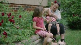 Stående av den lyckliga storfamiljen av olika utvecklingar som sitter utanför ett hus på en sommardag 4k stock video