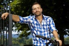 Stående av den lyckliga tillfälliga mannen på den utomhus- cykeln royaltyfria bilder