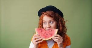 Stående av den lyckliga tonåringen som äter vattenmelon och ler på grön bakgrund lager videofilmer