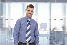Stående av den lyckliga unga affärsmannen på kontoret Fotografering för Bildbyråer