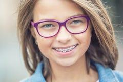 Stående av den lyckliga unga flickan med tand- hänglsen och exponeringsglas arkivfoto