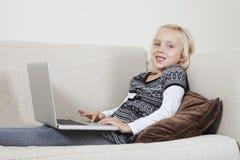 Stående av den lyckliga unga flickan som använder bärbara datorn på soffan Arkivfoton