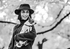 Stående av den lyckliga unga kvinnan med hunden utomhus i höst royaltyfri fotografi