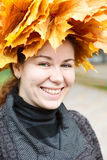 Stående av den lyckliga unga kvinnan med lönnkranen royaltyfri foto