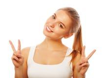 Stående av den lyckliga unga kvinnan som ger fredtecknet Arkivbilder