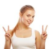 Stående av den lyckliga unga kvinnan som ger fredtecknet Arkivbild
