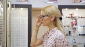 Stående av den lyckliga unga kvinnan som köper nya exponeringsglas på optikerlagret lager videofilmer