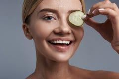 Stående av den lyckliga unga kvinnan som ler och rymmer stycket av gurkan fotografering för bildbyråer