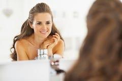 Stående av den lyckliga unga kvinnan som ser i spegel i badrum arkivbilder
