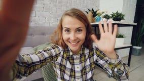 Stående av den lyckliga unga kvinnan som ser kameran, hållande grej och talar till vänner som ler och gör en gest direktanslutet stock video