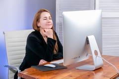 Stående av den lyckliga unga lyckade affärskvinnan på kontoret Hon sitter på tabellen, blickar på skärmen och drömmar Black Frida royaltyfri foto