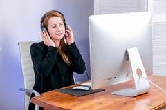 Stående av den lyckliga unga lyckade affärskvinnan på kontoret Hon sitter på tabellen med hörlurar och ser skärmen arkivfoton
