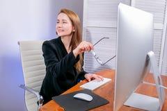 Stående av den lyckliga unga lyckade affärskvinnan på kontoret Hon sitter på tabellen, rymmer hennes exponeringsglas och pekar ti arkivfoton