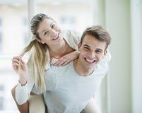 Stående av den lyckliga unga mannen som på ryggen hemma ger ritt till kvinnan Royaltyfria Bilder