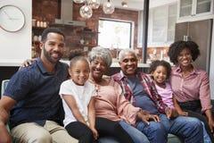 Stående av den mång- utvecklingsfamiljen som kopplar av på Sofa At Home Together royaltyfri fotografi