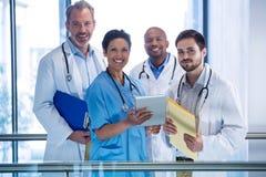 Stående av den mandoktorer och sjuksköterskan som använder den digitala minnestavlan i korridor royaltyfria bilder