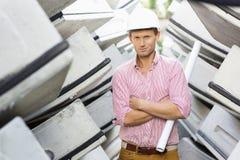 Stående av den manliga arkitekten som rymmer den hoprullade ritningen på konstruktionsplatsen Arkivbilder