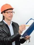 Stående av den manliga byggnadsarbetarekonstruktionsvicevärden i skyddande hjälm för exponeringsglas med en mapp av dokument och  Royaltyfri Bild