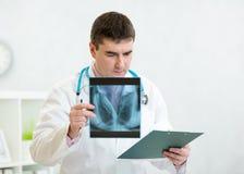 Stående av den manliga doktorn med skrivplattan på kontoret Arkivfoto