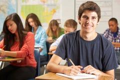 Stående av den manliga eleven som studerar på skrivbordet i klassrum Royaltyfria Foton