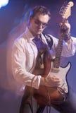 Stående av den manliga gitarristen Playing med uttryck Skjutit med St Arkivbild