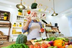 Stående av den manliga kocken som bär ett matlagningförkläde som jonglerar med colo Arkivbild