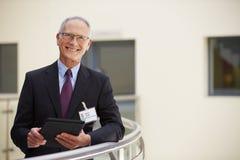 Stående av den manliga konsulenten Using Digital Tablet i sjukhus fotografering för bildbyråer