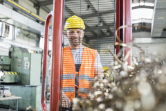 Stående av den manuella arbetaren som drar handlastbilen med stålshavings i fabrik Royaltyfri Fotografi