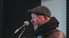 Stående av den medelåldersa mannen som sjunger sång i mikrofon stock video