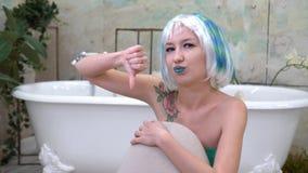 Stående av den missnöjda kvinnan i peruken som visar tummen ner i badrummet Royaltyfri Foto