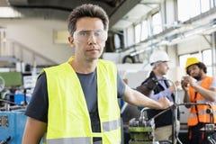 Stående av den mitt- vuxna arbetaren som bär den skyddande eyewearen med kollegor i bakgrund på bransch Royaltyfria Bilder