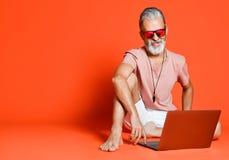 Stående av den moderiktiga pensionären som tycker om bruket av den nya bärbara datorn arkivbild