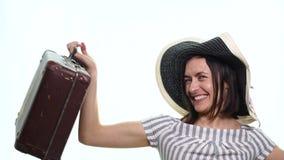 Stående av den moderiktiga unga kvinnlign i vide- hattanseende med resväska- och innehavpasset med biljetter över vit lager videofilmer