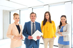 Stående av den mogna affärsmannen med kvinnliga kollegor i nytt kontor royaltyfria bilder