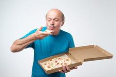 Stående av den mogna europeiska mannen som äter en skiva av pizza I hans händer rymmer han en ask av mat Inklusive snabb bana arkivfoton