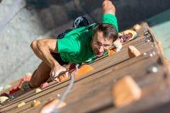 Stående av den mogna idrottsman nen på den extrema klättringväggen Arkivbilder
