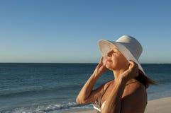 Stående av den mogna kvinnan med den vita hatten på stranden Royaltyfria Bilder