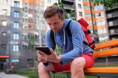 Stående av den mogna mannen i tillfälliga kläder genom att använda den digitala minnestavlan utomhus Arkivfoto