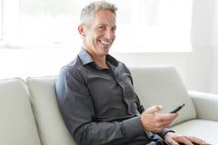 Stående av den mogna mannen som hemma kopplar av i soffa och mobiltelefon royaltyfri foto