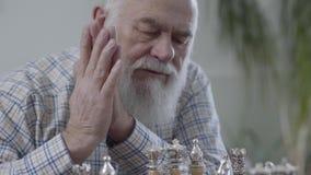 Stående av den mogna mannen som tänker vilket schackstycke för att göra en flyttning Två personer som spelar en lek av schac arkivfilmer