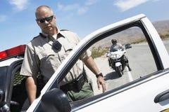 48 stående av den mogna polismannen som ut får från bilen Fotografering för Bildbyråer
