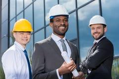 Stående av den multiethic gruppen av yrkesmässiga arkitekter i hårda hattar arkivfoto