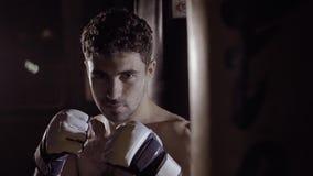 Stående av den muskulösa mannen som får klar till att boxas övning lager videofilmer