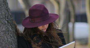 Stående av den mystiska flickan med hatten som döljer nära träd Värme väder En hacker som använder minnestavlan i parkera 4K lager videofilmer